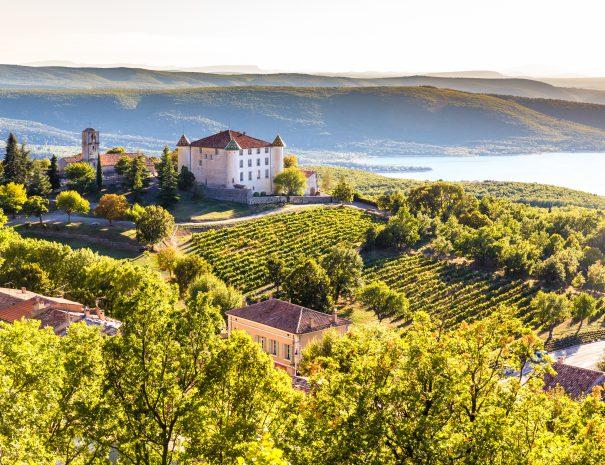 View Of Aiguines Village And Renaissance-style Chateau Overlooking Lac de Sainte Croix Lake-Alpes de Haute Provence,France